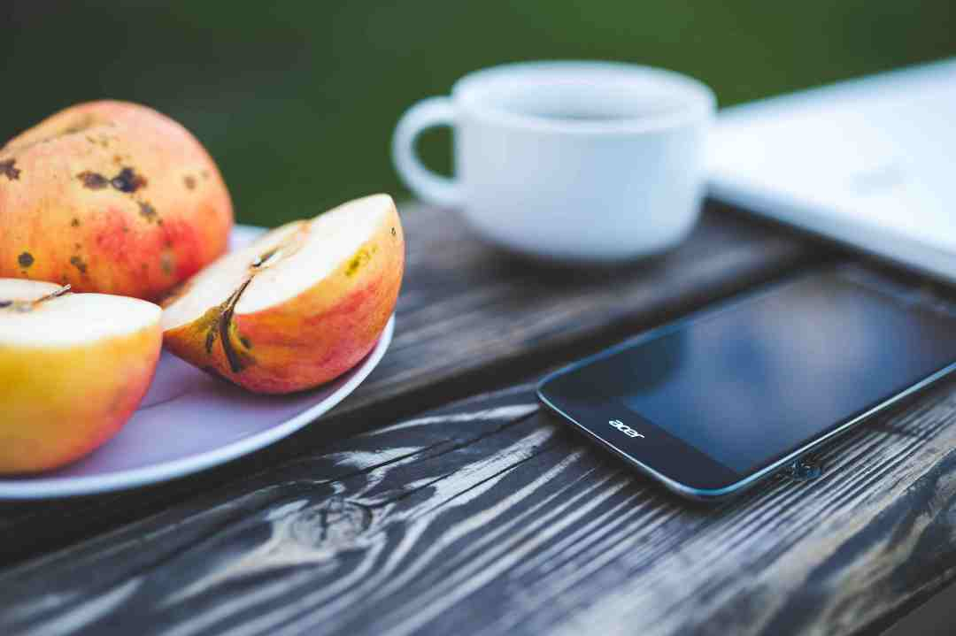 Phone, apple, coffee on the wooden table.jpg